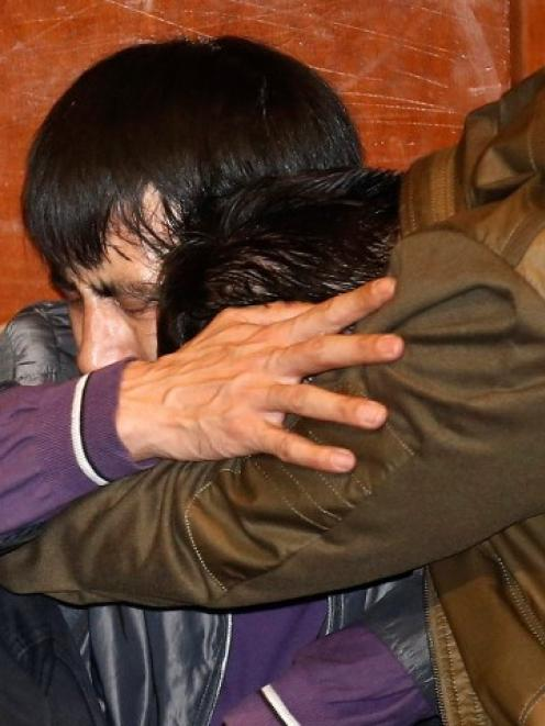 Relatives of passengers aboard the missing plane react after watching a broadcast of Malaysian...
