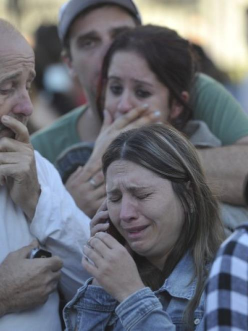 Relatives of victims cry in the southern city of Santa Maria, Brazil, where a nightclub fire...