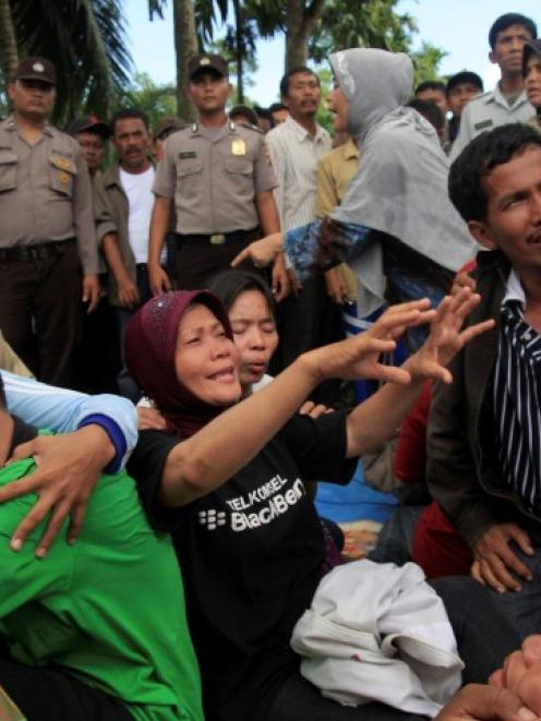 Relatives of victims of a plane crash react after receiving information that all of the...