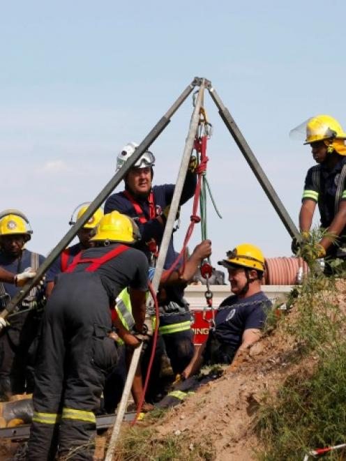 Rescue officials use hoists to remove debris as they work to rescue the trapped miners. REUTERS...