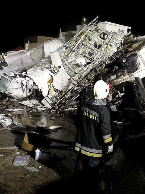 Rescue personnel survey the wreckage of TransAsia Airways flight GE222 on Taiwan's offshore...