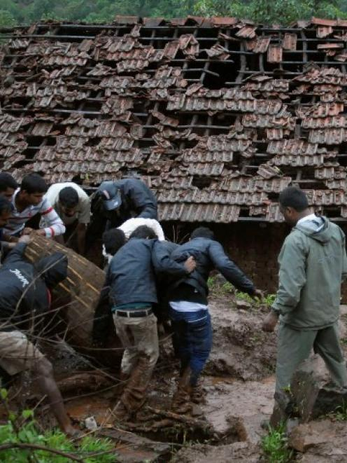 Rescue workers and volunteers clear the debris from the landslide site. REUTERS/Stringer
