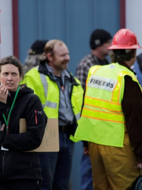 Rescue workers and volunteers involved in the search for people missing after the landslide...