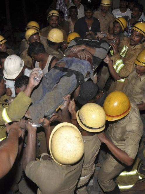 Rescue workers carry the body of an injured man at the site of a collapsed 11-storey building...