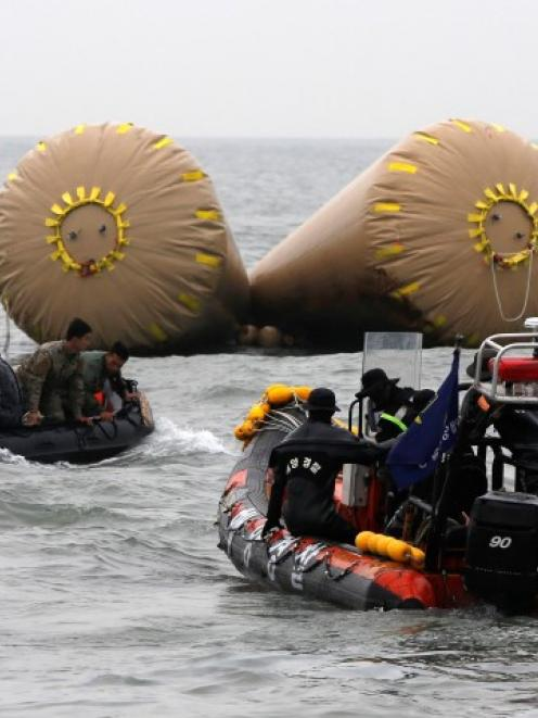 Rescue workers operate near floats where the capsized passenger ship Sewol sank in the sea off...