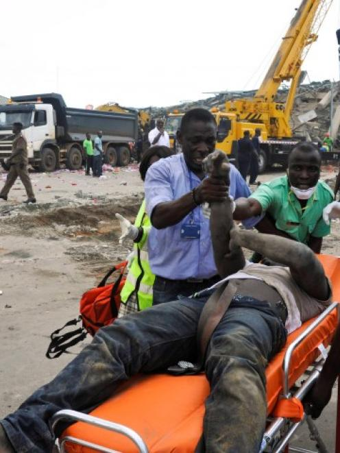 Rescue workers stretcher a wounded man out from the debris of a collapsed building in Accra,...