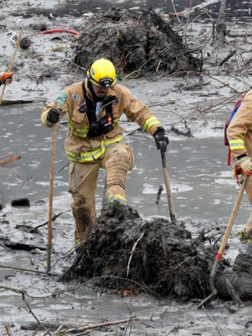 Rescue workers struggle through the mud looking for victims of the mudslide in Oso, Washington....