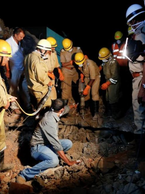 Rescue workers try to remove the body of a victim from the debris at the site of the collapsed...
