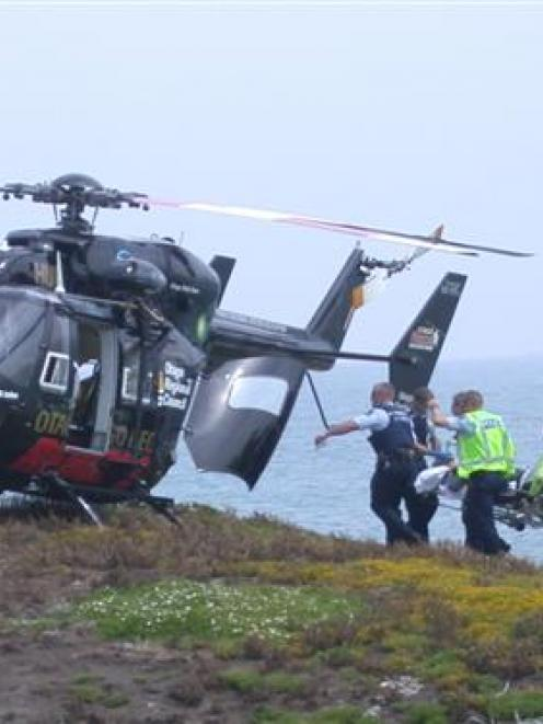 Rescuers carry an ill Kakanui man to the Otago Regional Rescue Helicopter on the island at the...