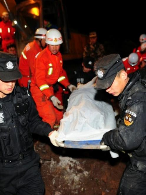 Rescuers carry the body of a victim after a landslide hit Zhenxiong county, Yunnan province on...
