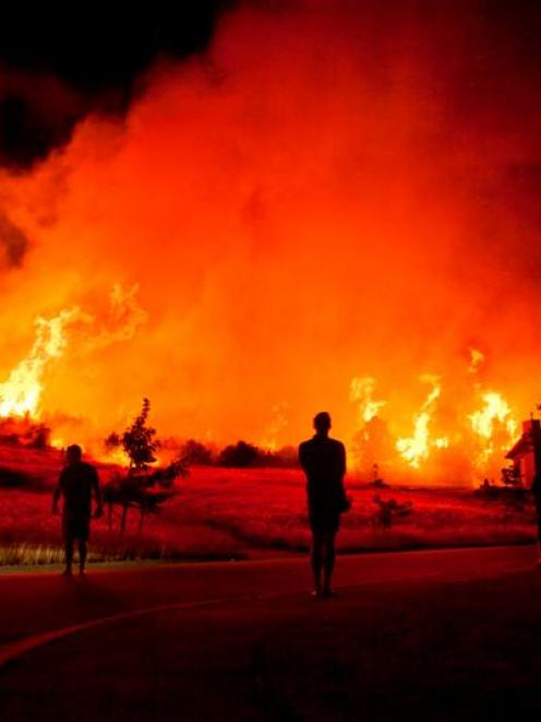 Residents are silhouetted against the blaze bordering the Mt Iron subdivision in Wanaka at 4.30am...