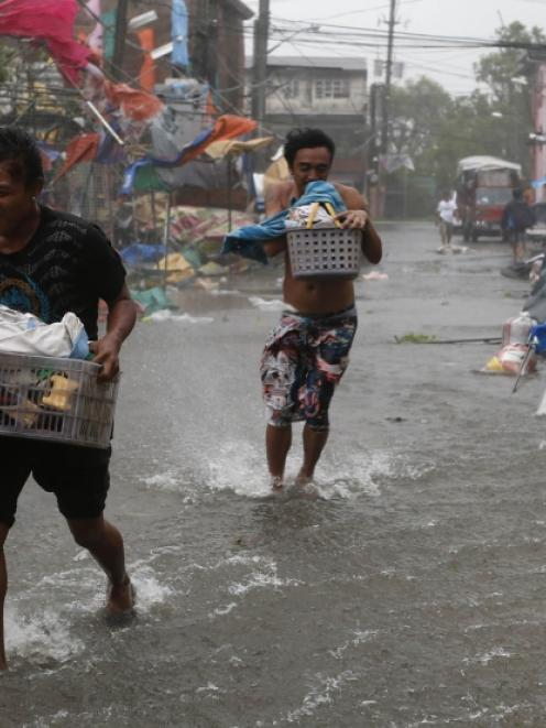 Residents carry their belongings as Typhoon Rammasun (locally named Glenda) hit the town of Imus,...