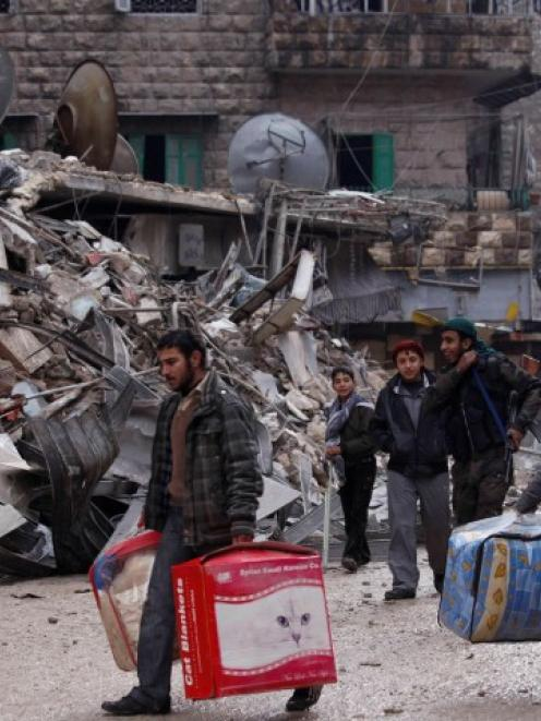 Residents evacuate their houses after being targeted by missiles fired by forces loyal to Syria's...