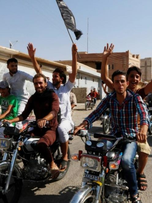 Residents of Tabqa city tour the streets on motorcycles, carrying flags in celebration after...