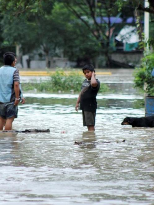 Residents wade through a flooded street in Poza Rica, in the Mexican state of Veracruz. REUTERS...