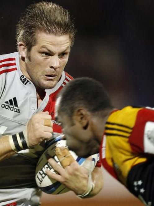 Richie McCaw, of the Crusaders, runs the ball at Sitiveni Sivivatu, of the Chiefs, in a Super...
