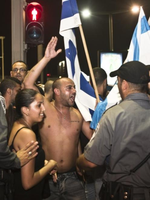 Right wing Israelis protest following an air raid siren warning of a rocket attack in Tel Aviv....