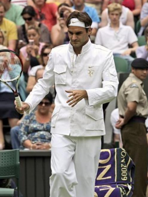 Roger Federer of Switzerland arrives for his first round match in his new warm-up outfit.  (AP...