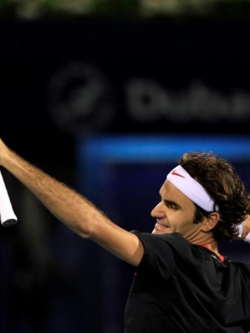 Roger Federer of Switzerland celebrates after beating Andy Murray of Britain to win the Dubai...