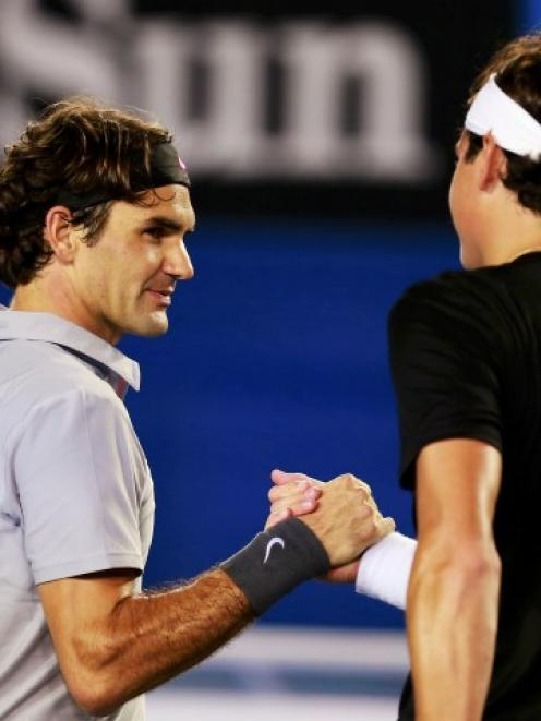 Roger Federer of Switzerland (L) shakes hands with Milos Raonic of Canada after defeating him in...