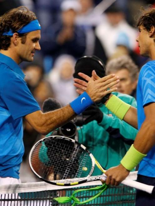 Roger Federer of Switzerland (L) shakes hands with Rafael Nadal of Spain after defeating him in...