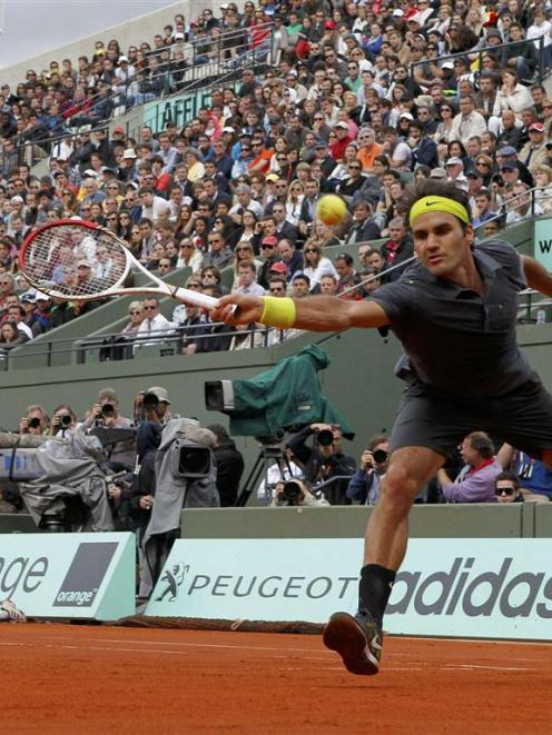 Roger Federer of Switzerland returns the ball to David Goffin of Belgium during the French Open...