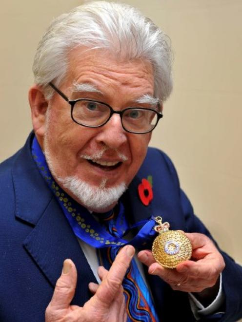 Rolf Harris holds the Officer of the Order of Australia award, which was presented to him by High...