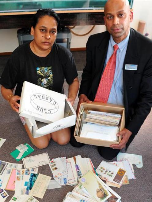 Romeni (left) and Dharama Sena look over the postcard covers, letters, envelopes and stamps they...
