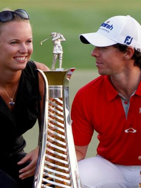 Rory McIlroy of Northern Ireland smiles at his girlfriend tennis player Caroline Wozniacki as he...