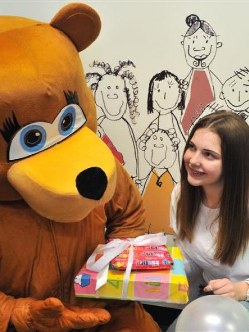 Rosaria Marsh (15), of Dunedin, gives presents to Foster Bear, the Child, Youth and Family mascot...