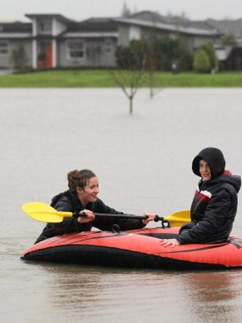 Rose McEwan, 16, and James McEwan, 12 paddle their inflatable lilo's on a flooded play ground in...