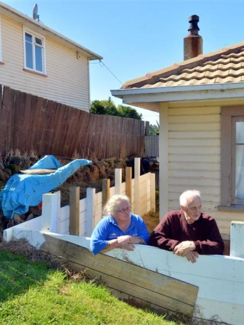 Rose McRobie and her father  examine the retaining wall  they had to build  in their backyard...