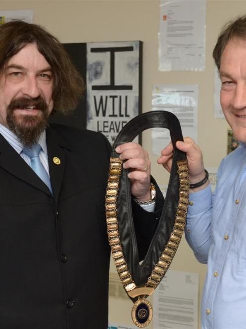 Rotary's new district governor Jonathan Usher (left) accepts the chain of office from Gary...