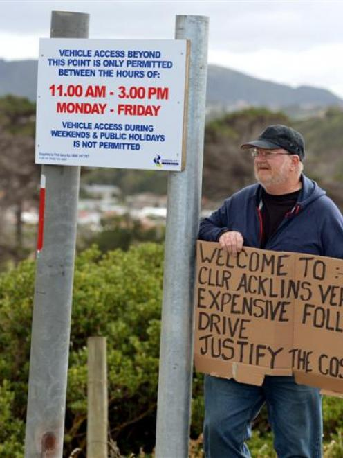 Roy Robertson holds a placard denouncing the Dunedin City Council's decision to reopen the road.