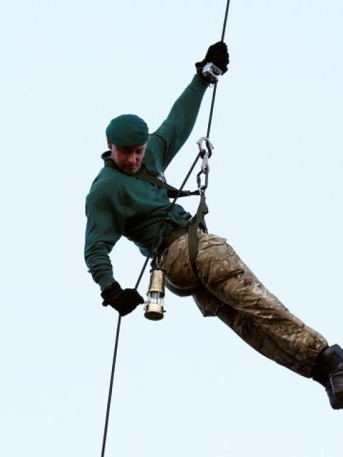 Royal Marine Martyn Williams carries the London 2012 Olympic flame inside a lantern as he abseils...
