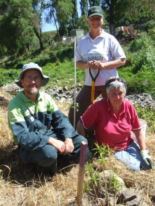 Russell Quinn, Marian Shore and Jan Armour plant native trees beside Oamaru Creek yesterday....