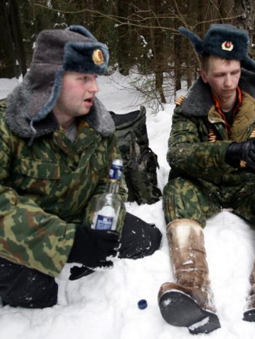 Russian men in army uniform drink vodka during celebrations for Maslenitsa (Pancake Week), also...