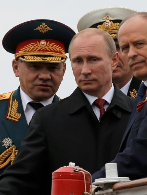 Russian President Vladimir Putin (C), Defence Minister Sergei Shoigu (L) and Russia's Federal...