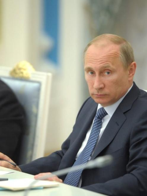 Russian President Vladimir Putin (R) chairs a meeting on economic and social issues in Moscow. At...