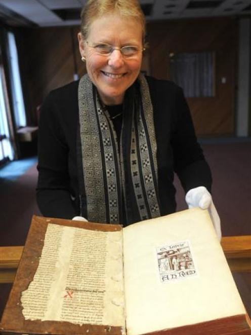 Ruth Lightbourne, curator of the Alexander Turnbull rare book collection, examines a 15th century...