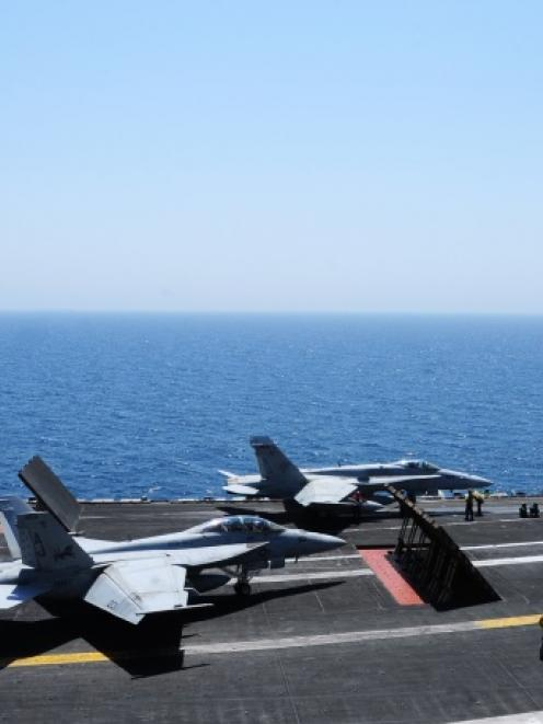 Sailors launch aircraft from the flight deck of the aircraft carrier USS George H.W. Bush (CVN 77...