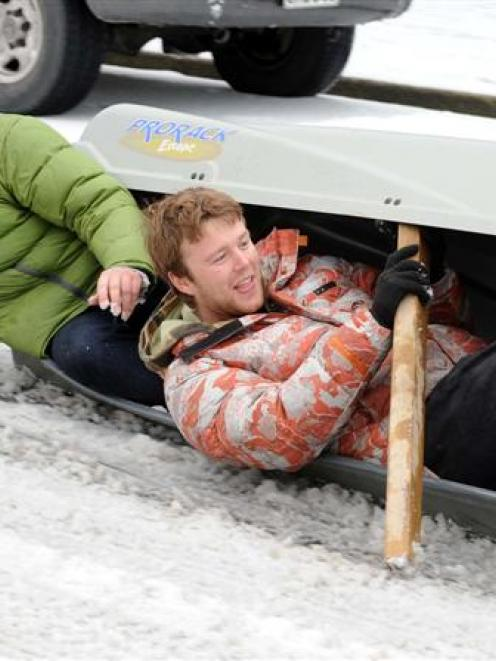 Sam Broadmore (left) and Josh Richardson improvise and slide on  a car carry pod on London St, in...