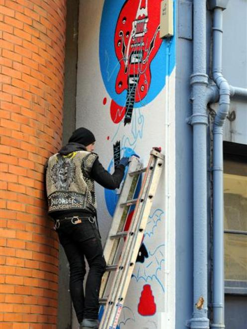 Sam Ovens, of Dunedin, wearing his distinctive studded vest as he works on a piece for the Vogel...