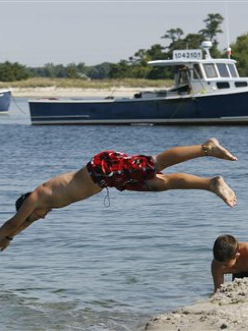 Sam Woodward, 12, left, dives over Jackman Mickiewicz, 12, into the water at Ferry Beach, Maine....