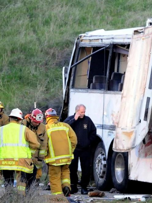 San Bernardino firefighters converge on the scene of a crash by a Mexico-bound tour bus in...