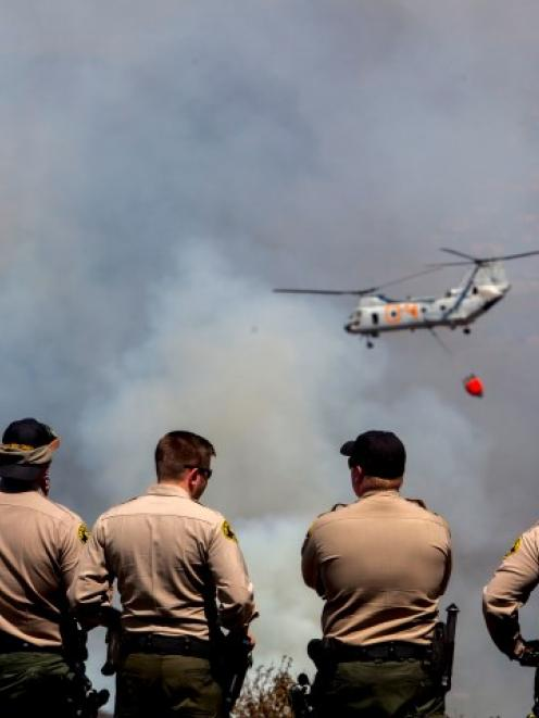 San Diego Sheriff's deputies watch as a firefighting helicopter flies across during the Cocos...