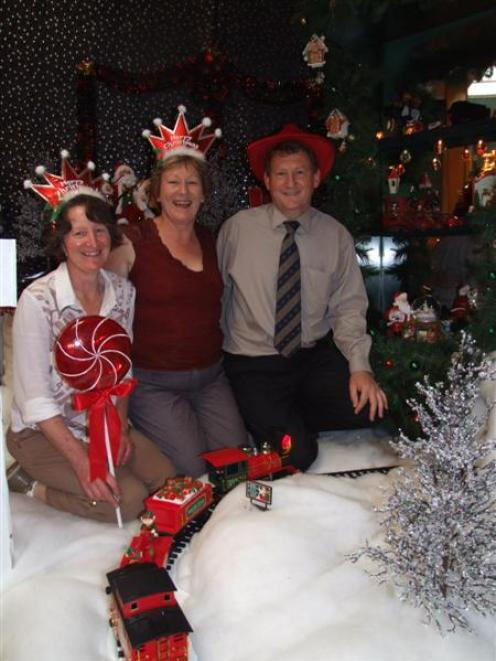 Sandra Payne (left), Anne and Paul Townend inspect the 2007 Christmas wonderland above the...