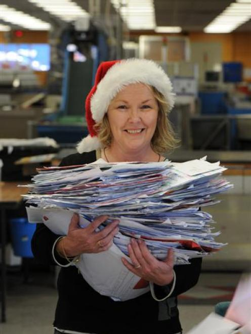 Santa's letter helper Colleen Eckhoff, of New Zealand Post, sorts through piles of Dear Santa...
