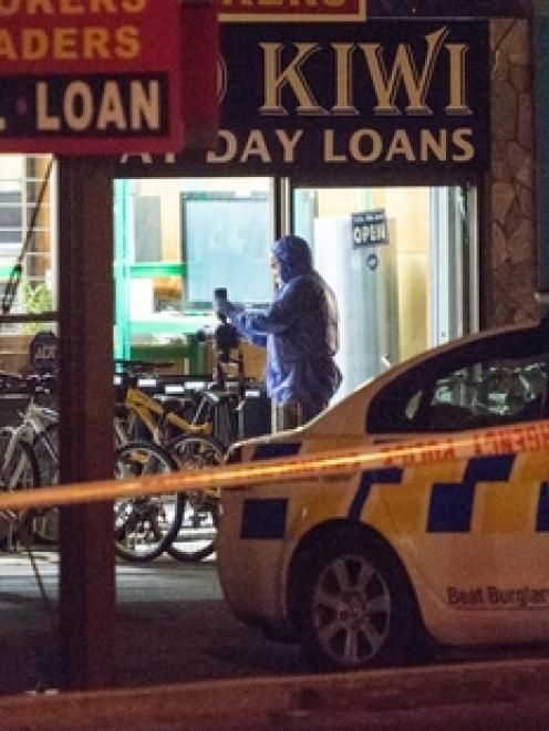 Scene of crime officers cordoned off the Ezy Cash store last night. Photo: NZ Herald/Chris Loufte