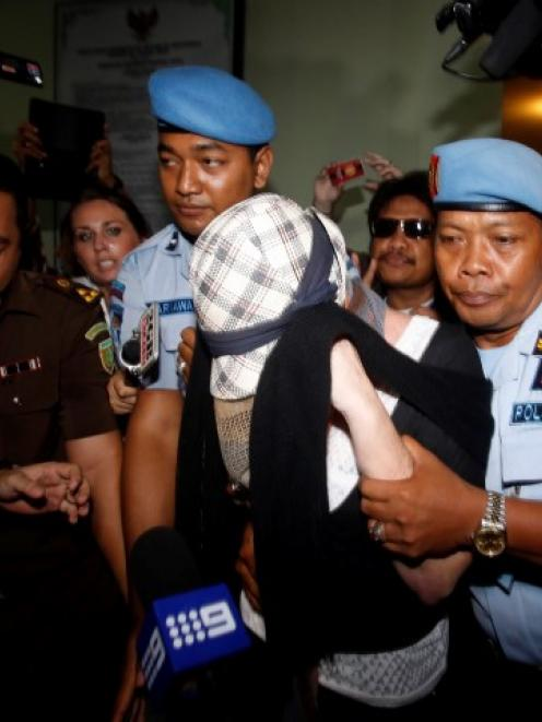 Schapelle Corby is escorted by police from the prosecutor's office in Denpasar following her...